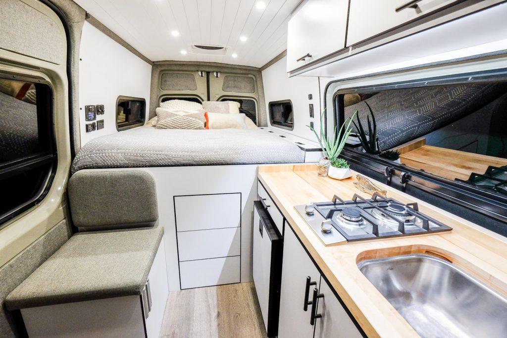 Cama, mesa y cocina acomodadas en un Sprinter